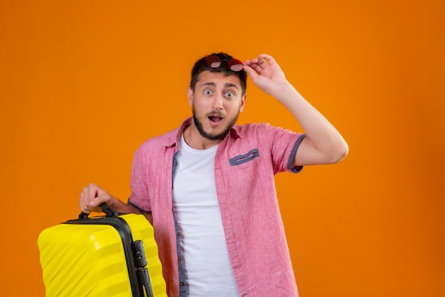 Jonge knappe reiziger kerel bedrijf koffer raakt zijn zonnebril op hoofd kijken camera verrast en verlaten staande over oranje achtergrond