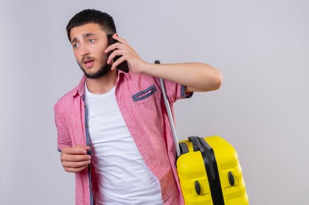 Jonge knappe reiziger kerel die bedrijfskoffer draagt ?? die op mobiele telefoon spreekt die verward status over witte achtergrond kijkt