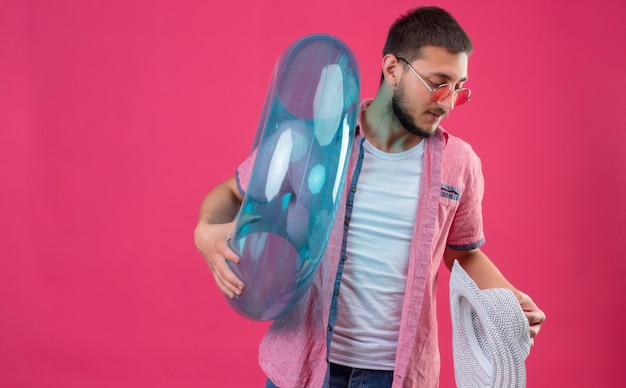 Jonge knappe reiziger kerel die zonnebril draagt ?? die opblaasbare ring en zomerhoed houdt die opzij kijkt met ernstige zelfverzekerde uitdrukking op gezicht dat zich over roze achtergrond bevindt