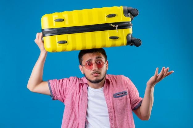 Jonge knappe reiziger kerel die zonnebril draagt ?? die zich met koffer op hoofd bevindt clueless en verward status met opgeheven wapens over blauwe achtergrond bevindt