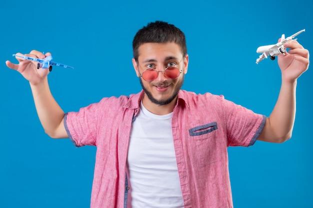 Jonge knappe reiziger kerel die zonnebril houdt die speelgoedvliegtuigen houdt die met hem spelen die op zoek gelukkig en positief glimlachend vrolijk staan over blauwe achtergrond