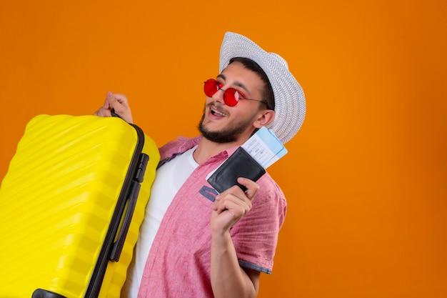 Jonge knappe reiziger kerel draagt een zonnebril in zomer hoed bedrijf koffer en vliegtickets op zoek zelfverzekerd en gelukkig lachend vrolijk klaar om te reizen staande over oranje achtergrond