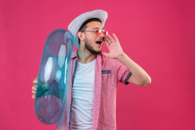 Jonge knappe reiziger kerel in zomerhoed die zonnebril draagt die opblaasbare ring houdt die schreeuwt of iemand met hand dichtbij mond roept die zich over roze achtergrond bevindt