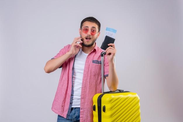 Jonge knappe reiziger man draagt een zonnebril bedrijf koffer en vliegtickets op zoek verward twijfels staande op witte achtergrond