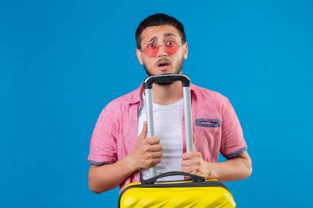 Jonge knappe reiziger man draagt een zonnebril bedrijf koffer kijken camera met verwarren uitdrukking op gezicht staande over blauwe achtergrond