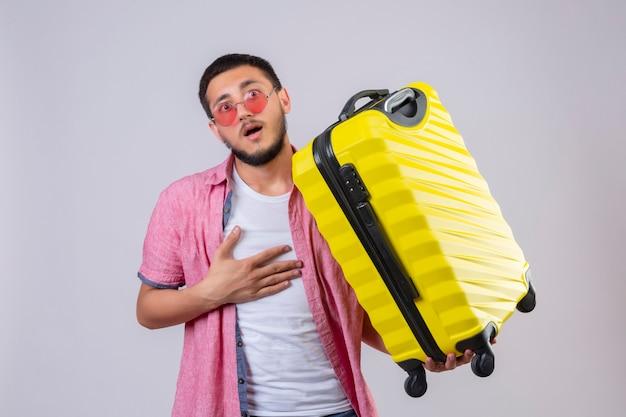 Jonge knappe reiziger man draagt een zonnebril met koffer op zoek verrast en verbaasd staande met hand oh borst op witte achtergrond