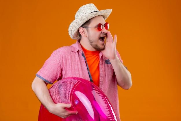 Jonge knappe reiziger man in zomer hoed met opblaasbare ring schreeuwen