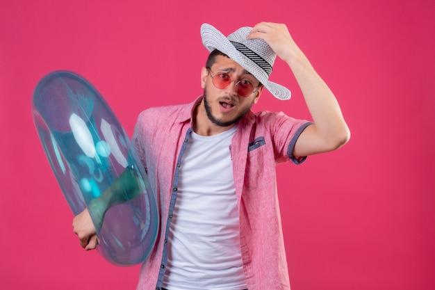 Jonge knappe reiziger man in zomerhoed dragen van een zonnebril met opblaasbare ring clueless en verward aanraken van zijn hoed geen antwoord staan over roze achtergrond