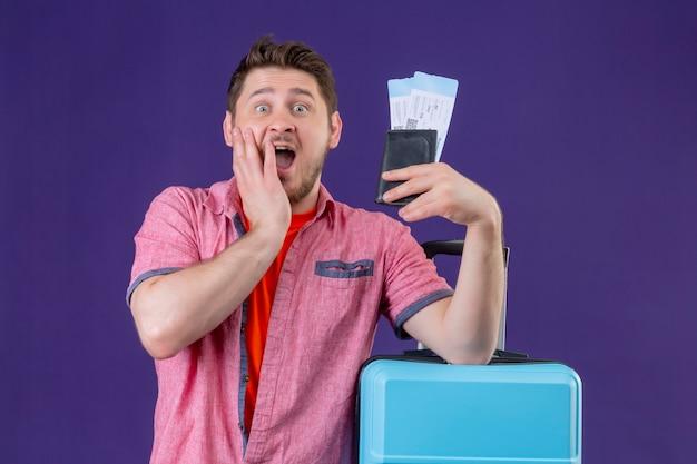 Jonge knappe reiziger man met blauwe koffer en kaartjes