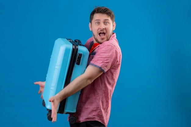 Jonge knappe reiziger man met blauwe koffer op zoek verward