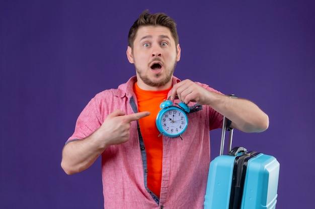 Jonge knappe reiziger man met blauwe koffer wijzend met vinger naar wekker in zijn andere hand