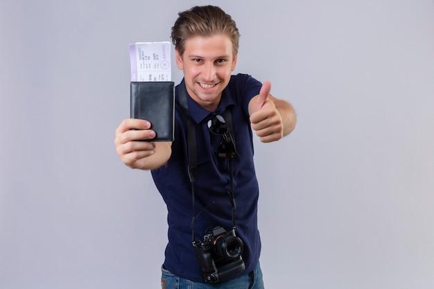 Jonge knappe reiziger man met camera houden van vliegtickets kijken camera met glimlach op gezicht blij en positief duimen opdagen staande op witte achtergrond