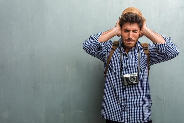 Jonge knappe reiziger man met een strooien hoed, een rugzak en een fotocamera voor ea