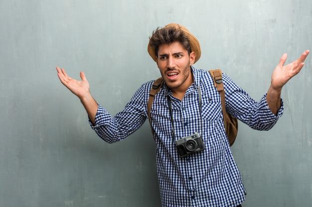 Jonge knappe reiziger man met een strooien hoed, een rugzak en een gekke fotocamera