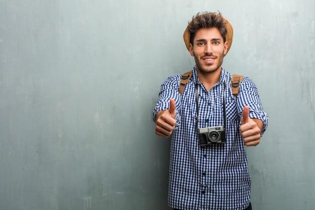 Jonge knappe reiziger man met een strooien hoed, een rugzak en een vrolijke en opgewonden fotocamera, glimlachend en het verhogen van haar duim, concept van succes en goedkeuring, ok gebaar