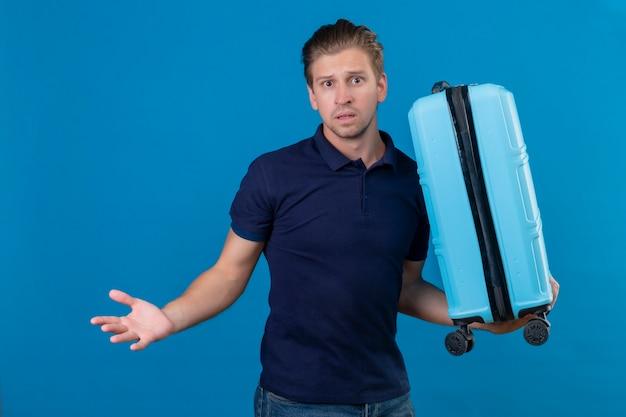 Jonge knappe reiziger man met koffer camera kijken met verwarren uitdrukking staande met armen opgeheven over blauwe achtergrond