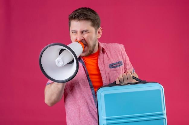 Jonge knappe reiziger man met koffer en megafoon schreeuwen tegen het