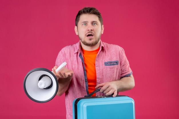 Jonge knappe reiziger man met koffer en megafoon