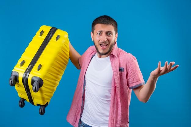 Jonge knappe reiziger man met koffer op zoek teleurgesteld staande over blauwe achtergrond