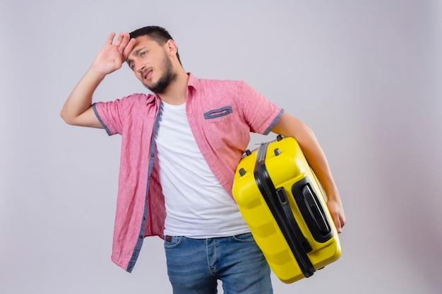 Jonge knappe reiziger man met koffer opzij kijken verveeld en moe met droevige uitdrukking op gezicht staande op witte achtergrond