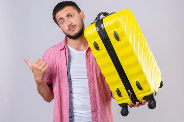 Jonge knappe reiziger man met koffer wijzend met vinger naar de kant camera kijken met verwarren uitdrukking op gezicht staande op witte achtergrond