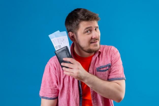 Jonge knappe reiziger man met vliegtuigtickets kijken zelfverzekerd en gelukkig lachend staande over blauwe muur