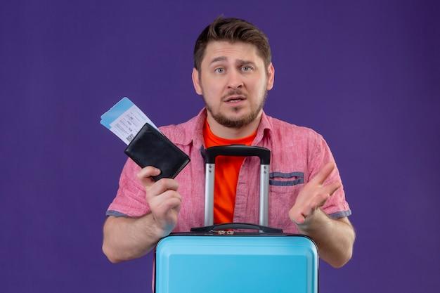 Jonge knappe reiziger man met vliegtuigtickets op zoek verward en onzeker