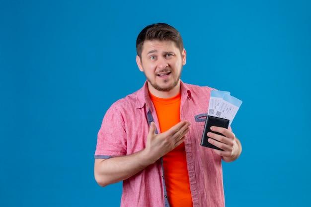 Jonge knappe reiziger man met vliegtuigtickets presenteren dan met arm van zijn hand met verwarde uitdrukking op gezicht staande over blauwe muur