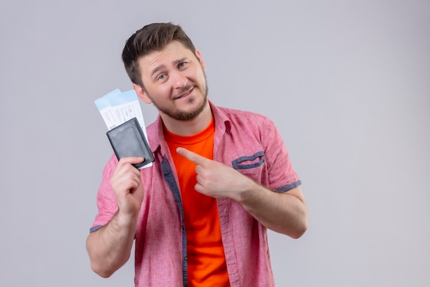 Jonge knappe reiziger man met vliegtuigtickets wijzend met vinger naar hen glimlachend positief en gelukkig staande over witte muur