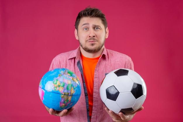 Jonge knappe reiziger man met voetbal en globe op zoek verward en onzeker