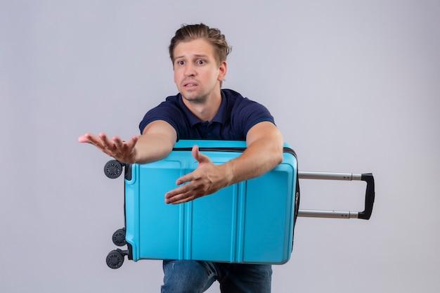 Jonge knappe reiziger man permanent met koffer opzij kijken met verwarren uitdrukking gebaren met handen op witte achtergrond