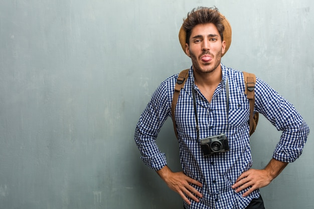 Jonge knappe reiziger mens die een strohoed, een rugzak en een uitdrukking van de fotocamera van vertrouwen draagt