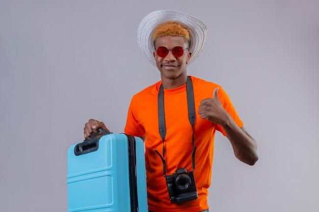 Jonge knappe reizigersjongen die in de zomerhoed een oranje t-shirt dragen die de reiskoffer glimlachen die vriendschappelijk tonen duimen omhoog die zich over witte muur bevinden