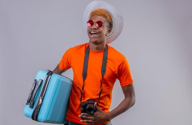 Jonge knappe reizigersjongen die in de zomerhoed oranje de reiskoffer van de t-shirtholding dragen die gelukkig en positief status over witte muur lachen