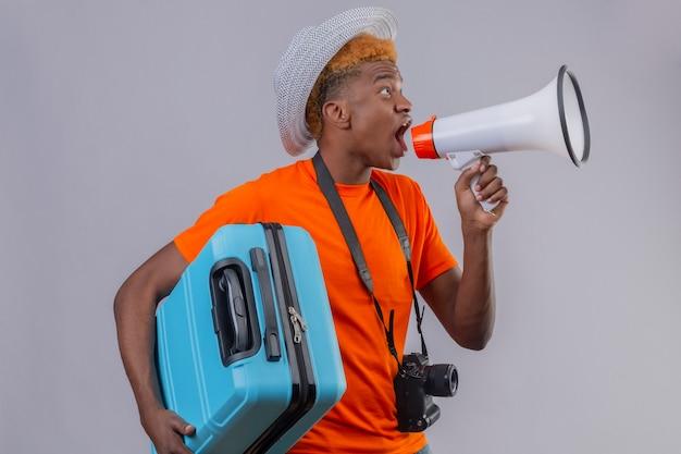 Jonge knappe reizigersjongen die in zomerhoed oranje de reiskoffer van de t-shirtholding dragen die aan megafoon schreeuwen die zich over witte muur bevindt