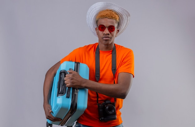 Jonge knappe reizigersjongen die in zomerhoed oranje de reiskoffer van de t-shirtholding met sceptische uitdrukking op gezicht dragen die zich over witte muur bevinden