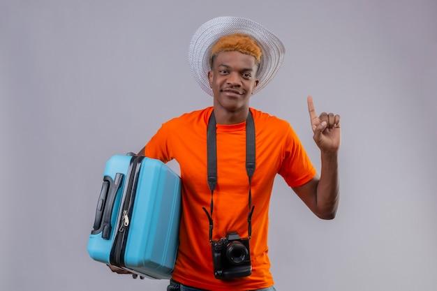 Jonge knappe reizigersjongen in zomerhoed die een oranje t-shirt draagt die de reiskoffer van de holdingsreis omhoog wijst die zelfverzekerd glimlachend over witte muur kijkt