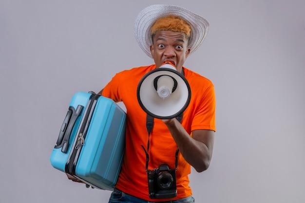 Jonge knappe reizigersjongen in zomerhoed die oranje t-shirt draagt die reiskoffer houdt die naar megafoon schreeuwt die geschokt over witte muur kijkt