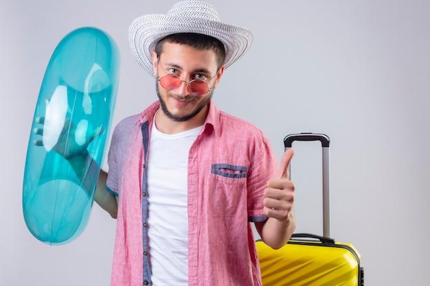 Jonge knappe reizigerskerel die in de zomerhoed opblaasbare ring houden kijkend het blije en gelukkige glimlachen die duimen tonen die met koffer over roze achtergrondkleur opstaan