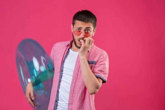Jonge knappe reizigerskerel die opblaasbare ring nerveus en beklemtoond bijtende spijkers houdt die zich over roze achtergrond bevinden