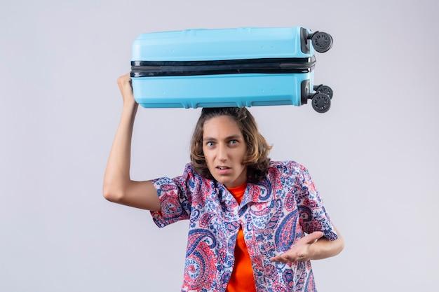 Jonge knappe reizigerskerel die zich met koffer op hoofd bevindt die bang en teleurgesteld over witte achtergrond kijkt