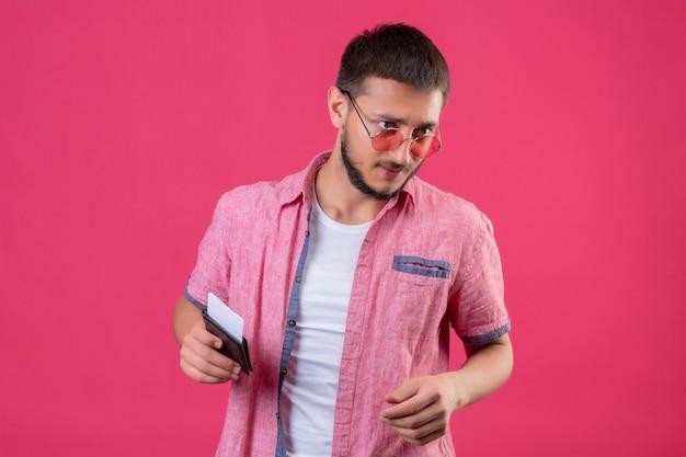 Jonge knappe reizigerskerel die zonnebril dragen die kaartjes houden kijkend opzij met zekere uitdrukking die zich over roze achtergrond bevinden