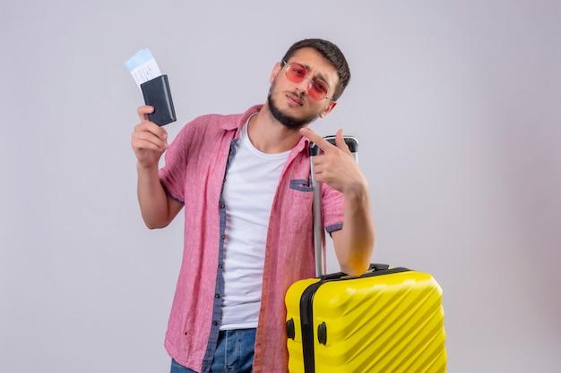 Jonge knappe reizigerskerel die zonnebril dragen die koffer en vliegtickets houden die camera met droevige uitdrukking op gezicht bekijken die zich over witte achtergrond bevinden
