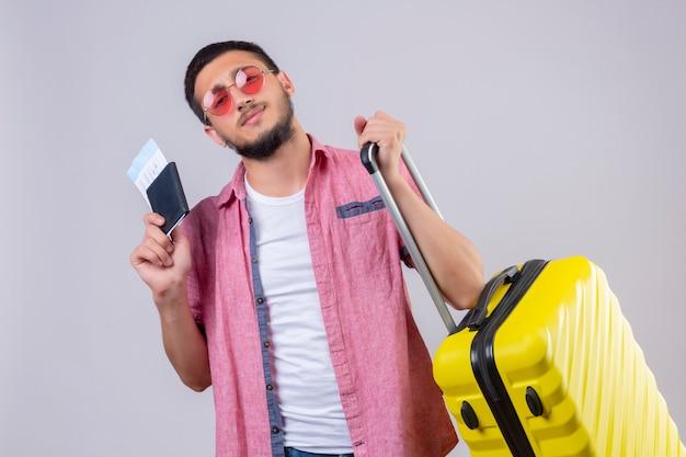 Jonge knappe reizigerskerel die zonnebril dragen die koffer en vliegtickets houden die camera met zekere glimlach bekijken die zich over witte achtergrond bevinden