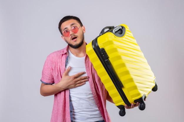 Jonge knappe reizigerskerel die zonnebril dragen die koffer houden kijkend verrast en verbaasd status met handoh borst over witte achtergrond