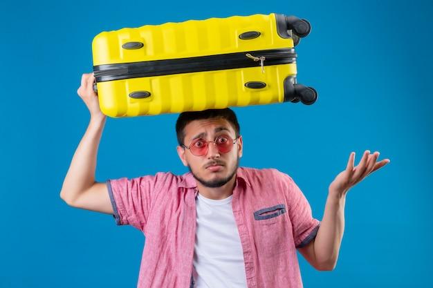 Jonge knappe reizigerskerel die zonnebril dragen die zich met koffer op hoofd bevinden clueless en verwarde status met wapens over blauwe achtergrond worden opgeheven