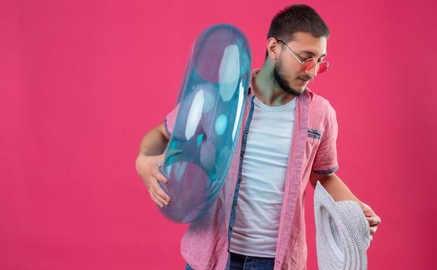 Jonge knappe reizigerskerel zonnebril dragen die opblaasbare ring en de zomerhoed houden kijkend opzij met ernstige zekere uitdrukking op gezicht die zich over roze achtergrond bevinden