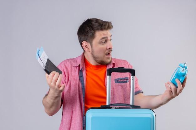 Jonge knappe reizigersmens die blauwe koffer en vliegtuigkaartjes houdt die wekker verward en teleurgesteld bekijken die zich over witte muur bevinden