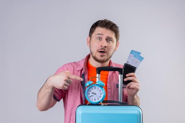 Jonge knappe reizigersmens die blauwe koffer en vliegtuigkaartjes met wekker verward en teleurgesteld houdt die zich over witte muur bevinden