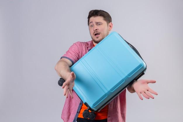Jonge knappe reizigersmens die blauwe koffer houdt die zich verward over witte muur bevindt